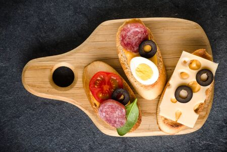 Open faced sandwich canape or crostini on a wooden serving board on dark stone  background closeup. Top view. Banco de Imagens