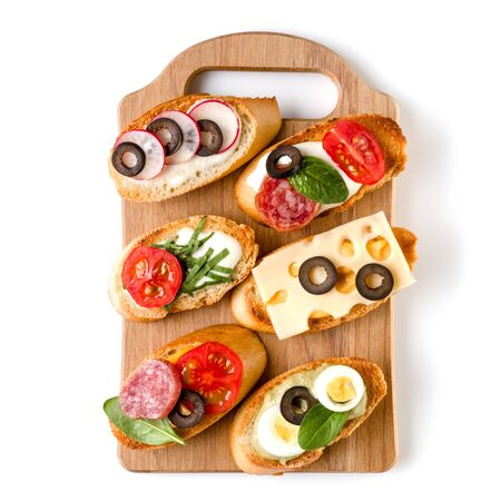 Open faced sandwich canape or crostini on a wooden serving board isolated on white background closeup. Top view. Banco de Imagens - 130164310