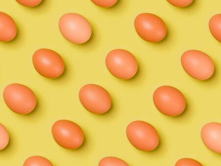 Eggs pattern on yellow background. Easter concept. Flat lay, top view. Food background. Pop art design, creative concept.. Creative layout . Stockfoto