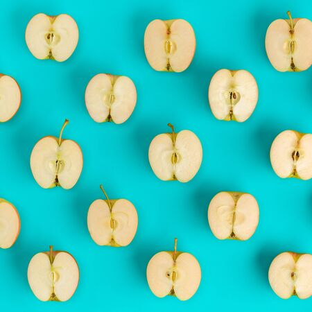 Fruit pattern of apple halves on blue background. Flat lay, top view. Food background..  Pop art design, creative summer concept.. Creative layout . Stockfoto