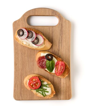 Open faced sandwich canape or crostini on a wooden serving board isolated on white background closeup. Top view.