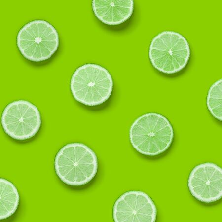 Fruit pattern of lime slices on green background. Flat lay, top view.. Pop art design, creative summer concept.. Creative layout . Stock fotó