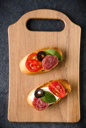 Open faced sandwich canape or crostini on a wooden serving board on dark stone  background closeup. Top view. Stock fotó