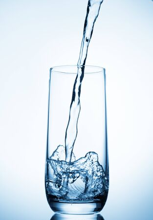 water pouring into glass on blue background