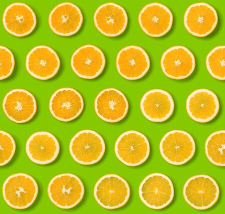 Seamless pattern of orange fruit slices on green background. Flat lay, top view. Food background. .  Pop art design, creative concept.. Creative layout .
