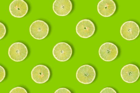 Fruit pattern of lemon slices on green background. Flat lay, top view.. Pop art design, creative summer concept.. Creative layout .