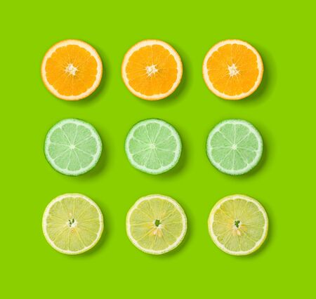 Citrus Fruits pattern on green background. Orange, Lime, Lemon slices background. Flat lay, top view.. Pop art design, creative summer concept.. Creative layout .