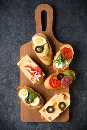 Open faced sandwich canape or crostini on a wooden serving board on dark stone  background closeup. Top view. Banco de Imagens - 130164385