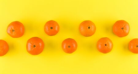 Fruit pattern of mandarin isolated on yellow background. Tangerine. Flat lay, top view.. Creative layout . Stockfoto