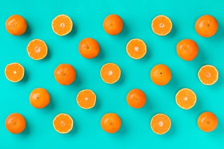 Fruit pattern of fresh mandarin slices on blue background. Flat lay, top view. Pop art design, creative summer concept. Half of citrus in minimal style. Tangerine.. Creative layout .