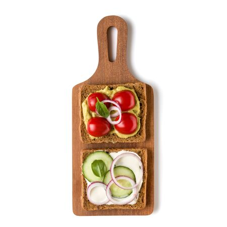 Open  faced vegetable sandwich canape or crostini on a wooden serving board  isolated on white