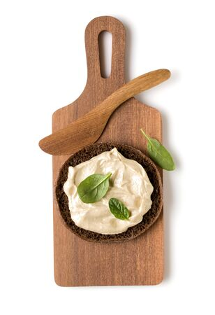 Open  faced hummus sandwich canape or crostini on a wooden serving board  isolated on white