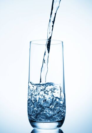 acqua che versa nel bicchiere su sfondo blu