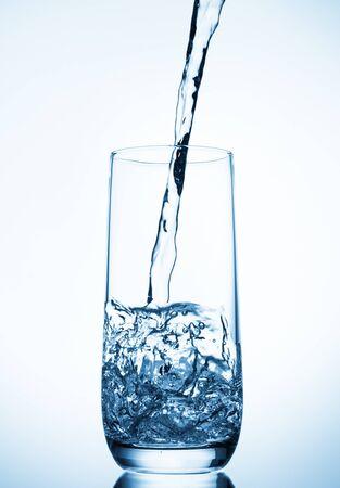 water gieten in glas op blauwe achtergrond