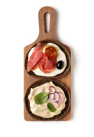 Open  faced sausage sandwich canape or crostini on a wooden serving board  isolated on white