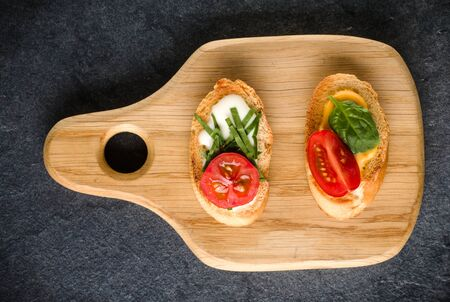 Open faced sandwich canape or crostini on a wooden serving board on dark stone