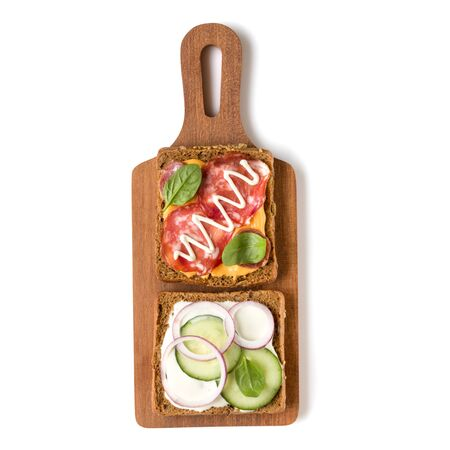 Open  faced sandwich canape or crostini on a wooden serving board  isolated on white