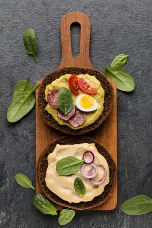 Open faced sausage sandwich canape or crostini on a wooden serving board  on dark stone background closeup. Top view.