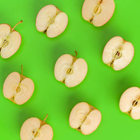 Fruit pattern on green background. Apple halves geometrical layout. Flat lay, top view. Food background..  Pop art design, creative summer concept.