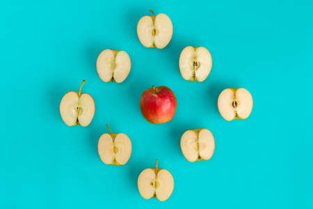 Fruit pattern on blue background. Apple halves geometrical layout. Flat lay, top view. Food background..  Pop art design, creative summer concept.