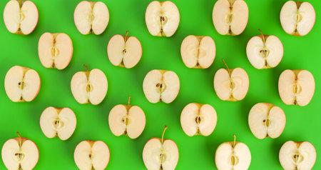 Fruit pattern of apple halves on green background. Flat lay, top view. Food background..  Pop art design, creative summer concept. Standard-Bild
