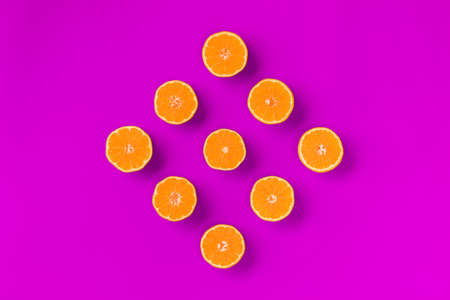 Fruit pattern of fresh orange tangerine or mandarin on lilac background. Flat lay, top view. Pop art design, creative summer concept. Citrus in minimal style.