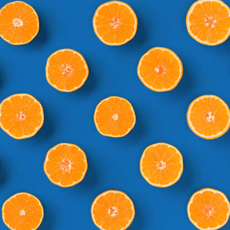 Fruit pattern of fresh orange tangerine or mandarin on blue background. Flat lay, top view. Pop art design, creative summer concept. Citrus in minimal style. Standard-Bild
