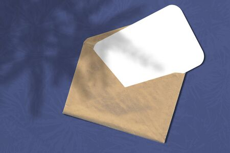 Envelope with a sheet of paper on a blue background. Layout with the imposition of the shadow of the Christmas tree. Natural light casts a shadow from above.