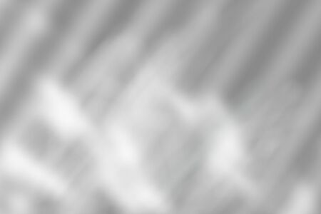 Blurred abstract background. Shadow from the window with sunbeams on the white wall. Black and white image to overlay a photo or Mockup.