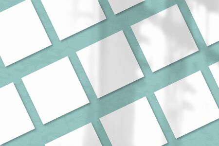 Several square sheets of white textured paper against a blue-green wall. Natural light casts shadows from the window. Flat lay, top view