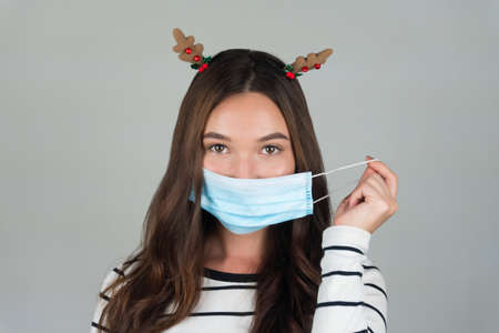 Beautiful young brunette with a medical protective mask on a gray background.