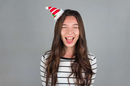 A happy young woman with Christmas decoration in her hair looks into the camera. Celebrating Christmas and New Year. High quality photo Archivio Fotografico