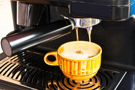 brewed: A ceramic cup of freshly brewed strong coffee pouring from coffee machine  Stock Photo