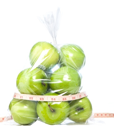 Green apples with tape measurment isolated background photo