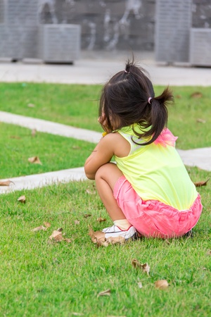 girl squatting: Baby girl squatting on grass in park