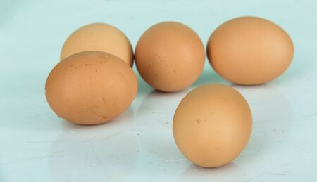 Five eggs on blue table photo