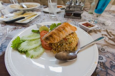 spicy rice fried with salmon on top in resturant