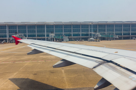 Aircraft wing view from inside plane with aire port at Yangon in Myanmar