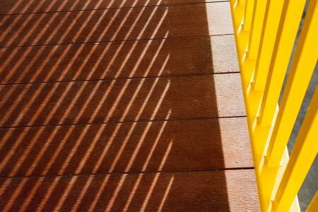 yellow metal porch with shadow sunlight on wood floor