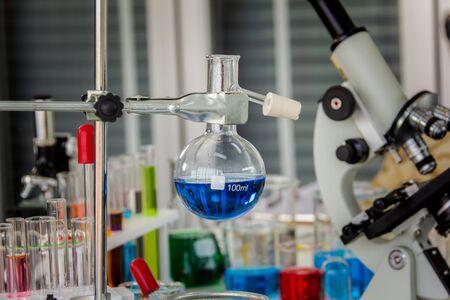 Chemische Destillationsgläser mit Mikroskopen in einem Labor mit roten, orangen, blauen Chemikalien im Becherglas und Röhrchen auf dem Operationstisch