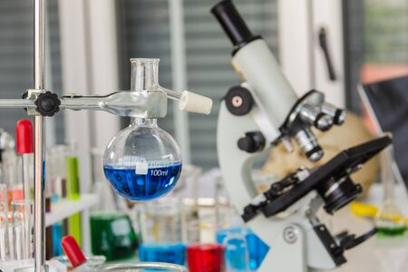 Chemical distillation glasses with microscopes placed in a laboratory with red, orange, blue chemicals in the beaker and tubes placed on the operating table Standard-Bild