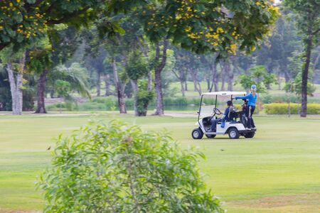Professional golf men ride electric car by woman caddies stand at back side into of a golf course with glittering yellow grass during the day