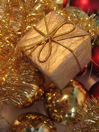 Golden christmas gift box on golden christmas balls background photo