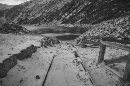 rail track: A disused rail track covered in snow at the bank of Norwegian fjord. During warmer months it is now used to launch boats in the fjord.