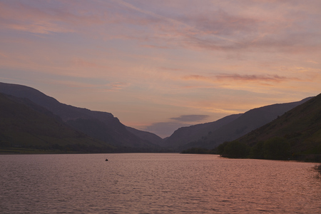 snowdonia: Glowing sky over Tal-y-Llyn lake in Snowdonia, North Wales, at daybreak on a windy day in May.