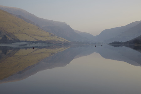 still water: Mountains reflecting in the still water of Tal-y-Llyn lake in Snowdonia, North Wales, on a calm summer morning.