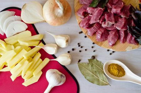carnes y verduras: la carne de vacuno se corta en trozos en un tablero de madera y cepilló las rodajas de patata y las cebollas, el ajo y una cucharada de especias y etc sobre un fondo blanco