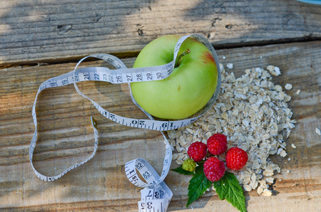 Green Apple wrapped with measuring tape next to the raspberry with leaves and a bunch of oatmeal on wooden boards