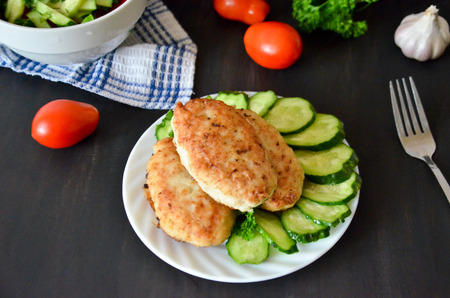 catfish: patties of fish next to sliced cucumbers in a dish and the vegetables next to the black
