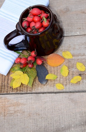 A full Cup of berries of rose hips on wooden boards next autumn assorted leaves and berries of wild rose and tea towel laid out